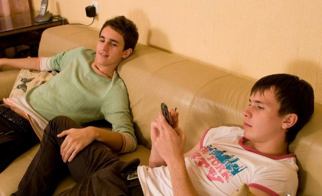 Cute young guys hanging out on the couch