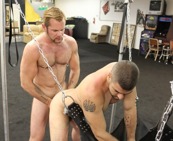 Dominic bends over the sling to take Tober's cock in his ass