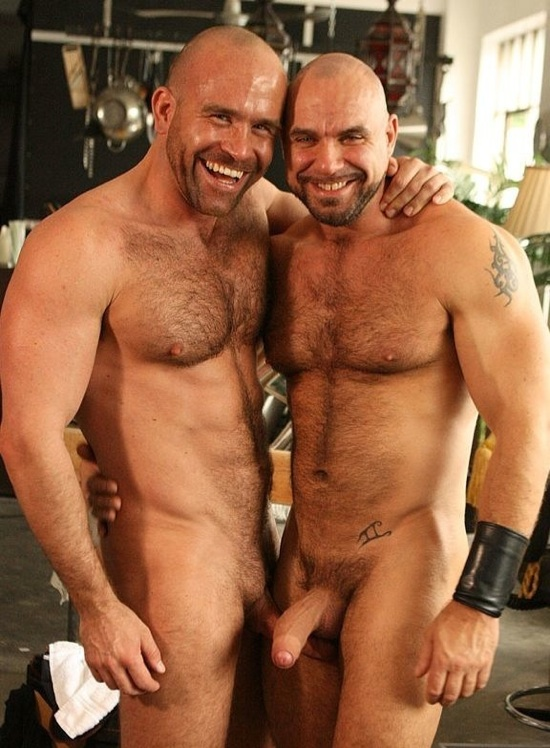 Two hairy, beefy, uncut and hung hunks hug with their erect dicks out.