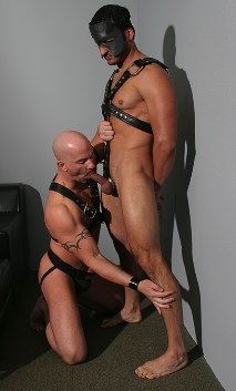Tattooed bald guy on his knees sucking a masked leatherman's dick