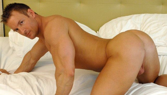 Smooth bodybuilder on all fours in bed
