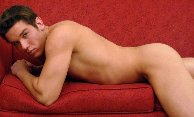 Smooth young jock Ryan Mackton laying nude on sofa and staring at camera.