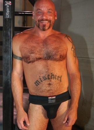 Tatted Mischeif in a black jockstrap