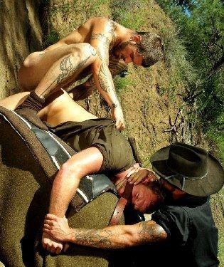 Cowboy holds down a rape victim while a tattooed guy fucks him