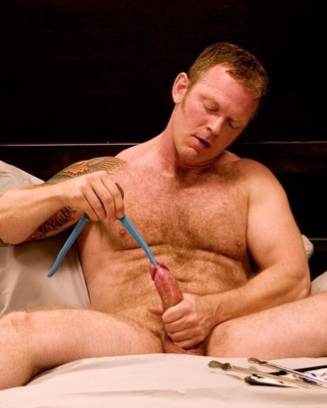 Lee Dakota inserting the handle on a pair of pliers into his piss slit