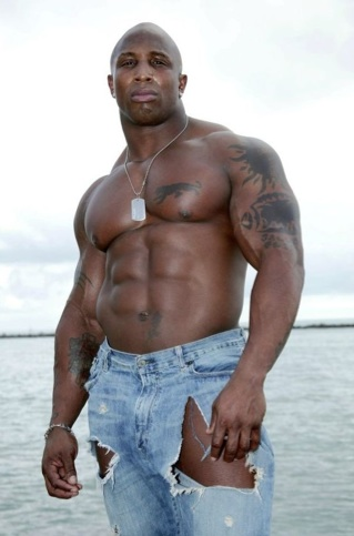 Beefy Black bodybuilder shirtless in ripped jeans