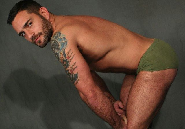 bearded man with tattoo wearing green briefs