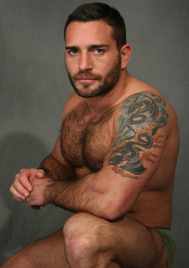man with beard shows hairy chest and smoldering look