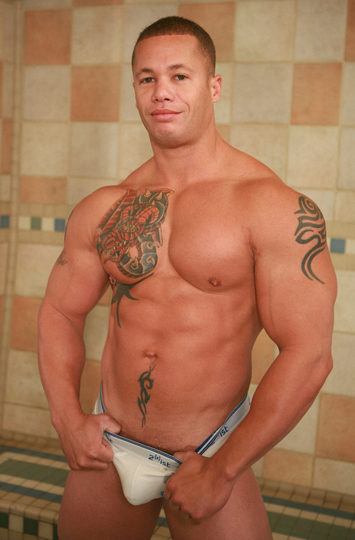 muscle hunk smiles and shows a bit of cock