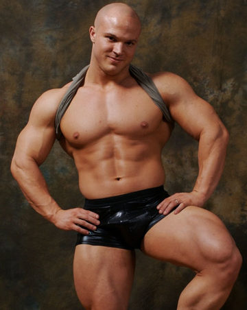 Beefy young bodybuilder Kyle Stevens shows off his chest anc quads