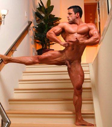 Fisicoculturista perfectamente definido, Alejandro de la Guardia posa para nosotros en bolas con su mano en la baranda de la escalinata