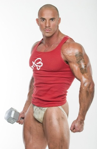 Bodybuilder Vin Marco in a tank top and a jockstrap holding a barbell