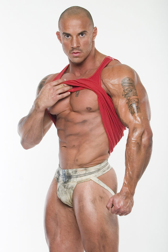 Body builder Vincent Marco pulling up his tank top showing his cheseled abs and dirty jockstrap