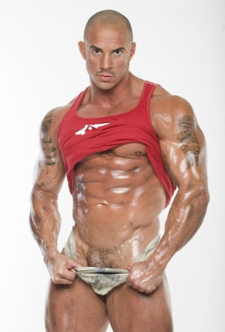Tatooed bodybuilder oiled, pulling down his jock strap showing his trimmed pubes