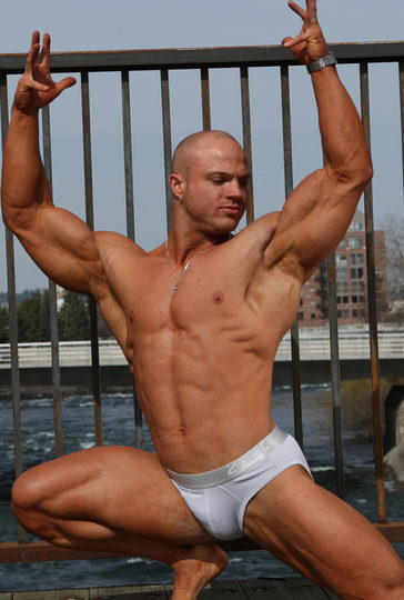 Beffy bald hunk pushes his hands in the air.