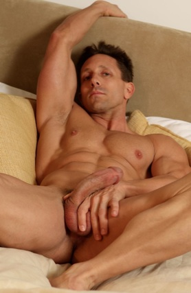 Muscular Arron Austin laying in bed holding his dick