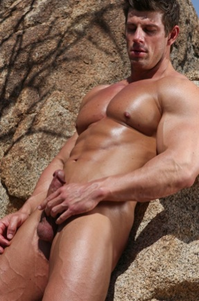 Muscle stud Zeb Atlas holds his cock while on a rock.