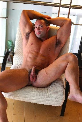 Smooth bodybuilder with hard on in chair