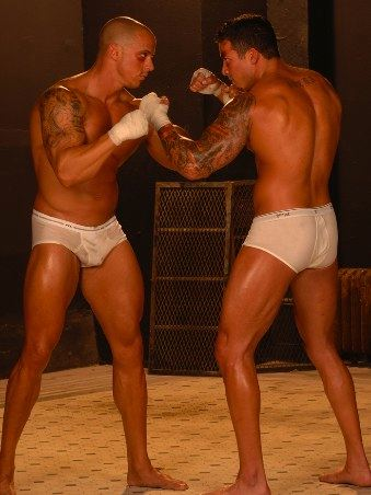 Tattooed bodybuilders in underwear trade punches