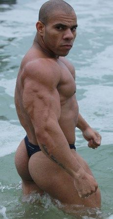 Hot bodybuilder in a thong in the surf at the ocean