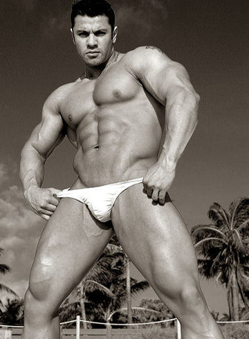 Massive bodybuilder posing in a tiny swimsuit