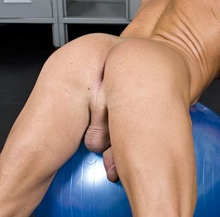 Ripped stud leans over his exercise ball to show his smooth tight ass
