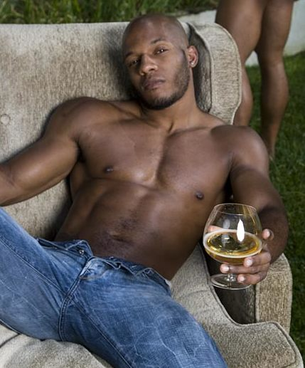 Hunky Black guy relaxes with a drink outside