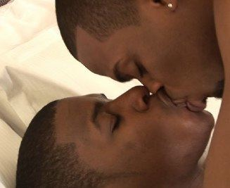 A couple of black boys kiss in bed