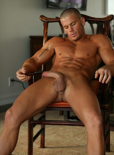Super buff body builder relaxes in chair with thick cock