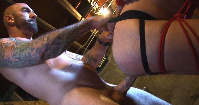 Tattooed top Drew Sebastian fucks a bound bottom with his huge cock